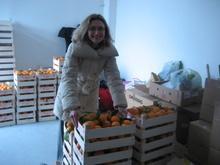 una partecipante ai gas prende una cassetta di arance