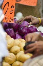 un mercato con delle mani in primo piano che prendono la verdura