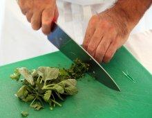 un uomo intento nell'affettare le verdure