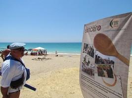 partecipanti sulla spiaggia e cartello della compagnia