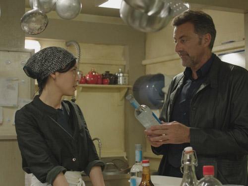 Due persone parlano in una cucina