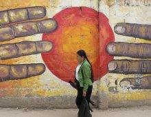 murales con due mani che si cercano davanti a un sole rosso