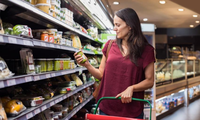 donna che legge le etichette dei prodotti mentre fa la spesa