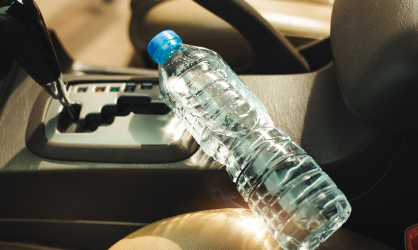 bottiglia d'acqu in auto sotto il sole