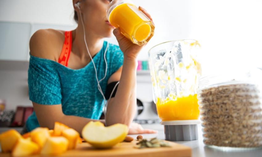 donna che fa colazione con succo d'arancia