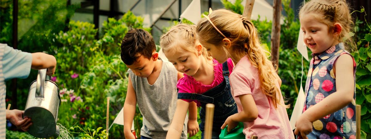bambini che innaffiano il giardino