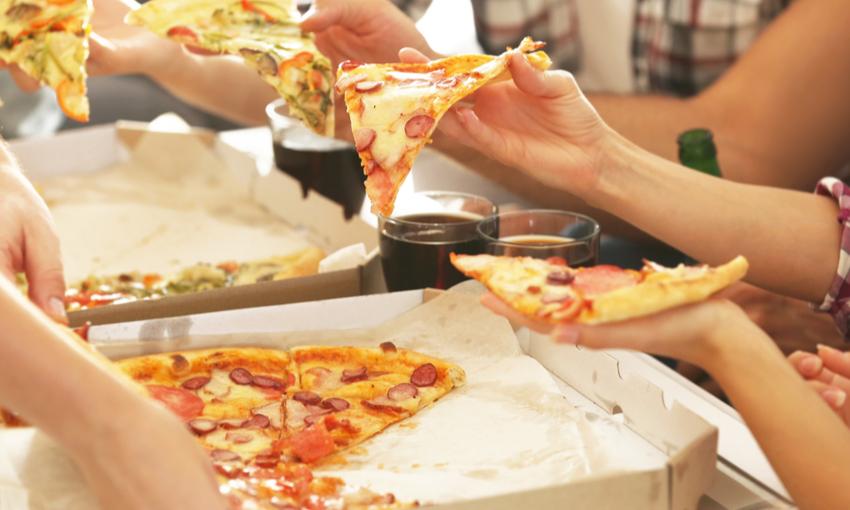 ragazzi che mangiano la pizza dal cartone