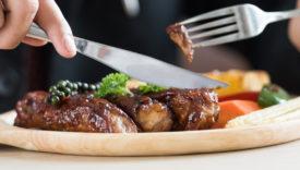 persona che mangia un piatto di carne