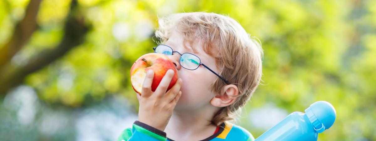 Bambino con occhiali che mangia una mela