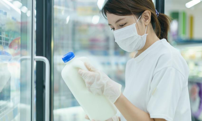 Donna con mascherina che compra il latte