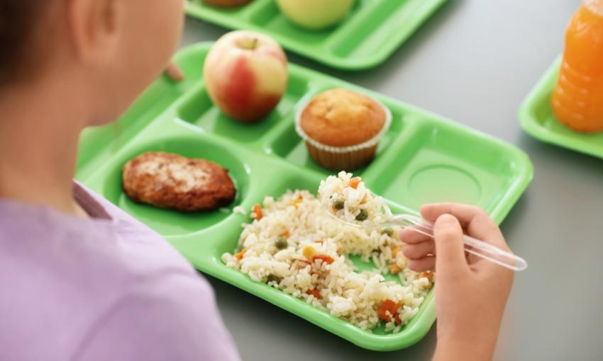 Bambino che mangia pranzo a scuola